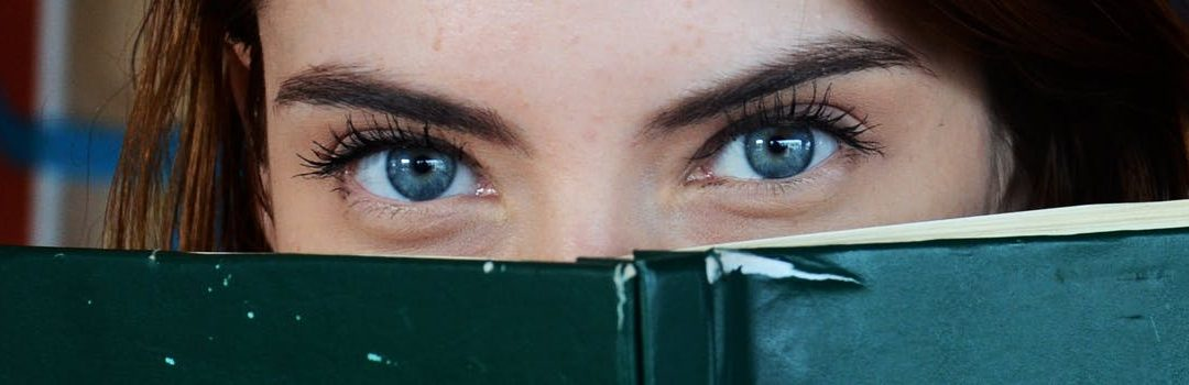 Woman looking at book to discover Yoni For Beginners