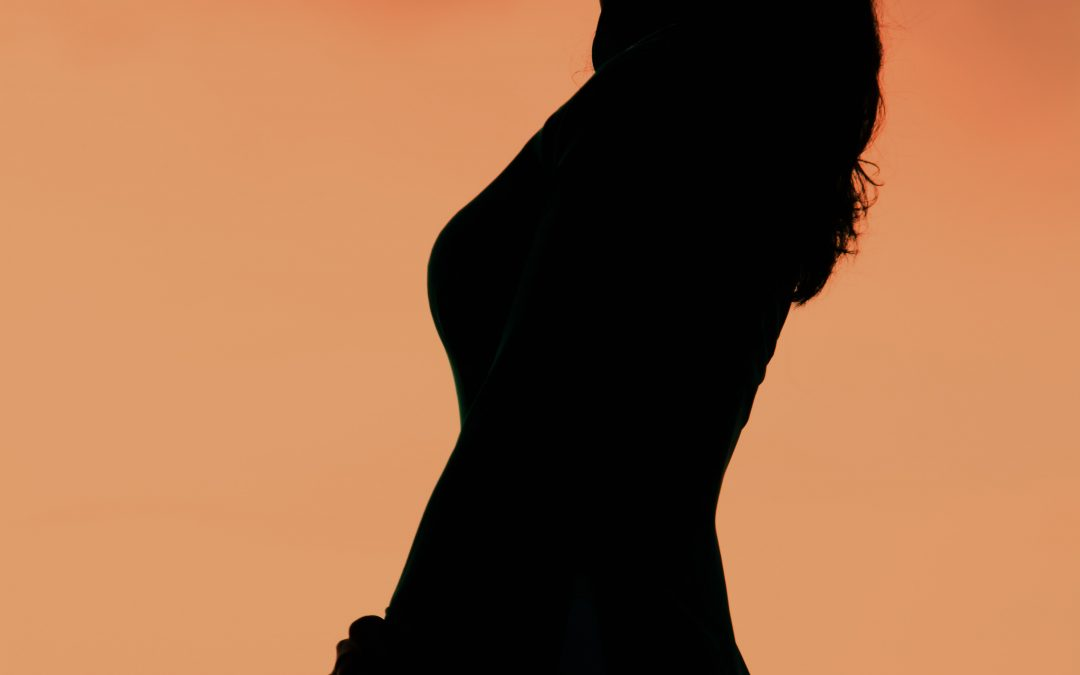 silhouette of woman standing sideways with orange background